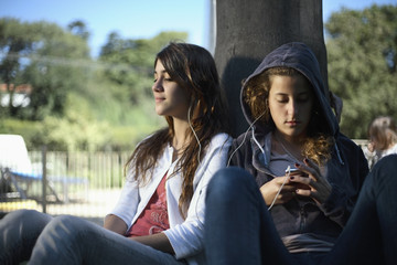 Two girls leaning against a tree with an MP3 Player
