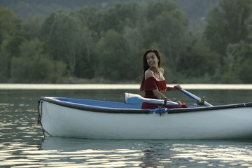 Woman in gown rowing a boat in lake