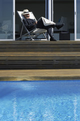 Man sleeping on deck by infinity pool
