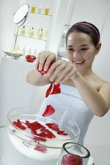 Woman putting flower petals into a bowl of milk