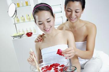 Two women putting flower petals in bowl of milk