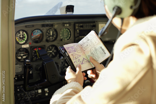 Pilot looking at passport in cockpit