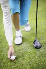 Woman holding golf club putting down golf ball