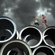 Two relay runners going across large cylinders