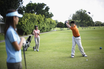 Three people playing golf