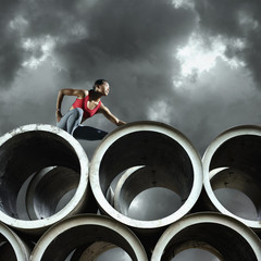 Runner leaning on large cylinders