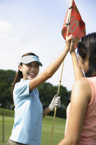Two women playing golf