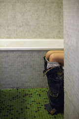 Girl in bathroom with only knees showing
