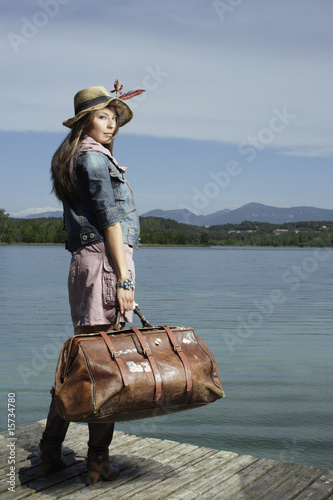 Woman standing on dock with large bag