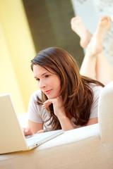 Frau am Sofa liegend mit Laptop, konzentriert