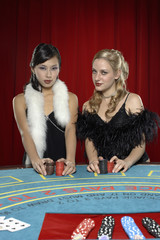 Two women with betting chips at casino table