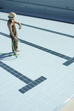 Man standing in empty pool with hose