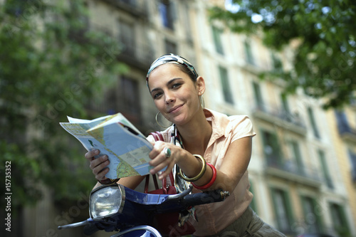 Woman on scooter with a map outdoors