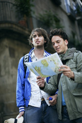Two men looking at a map outdoors