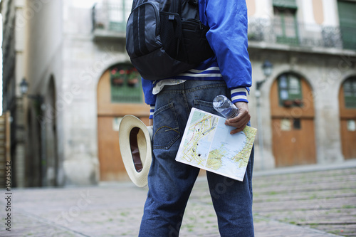 Man holding map hat and bottle of water outdoors