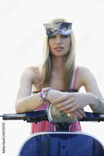 Woman sitting on a scooter after a party