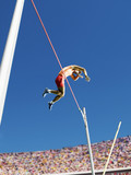 Athlete in mid air doing pole vault