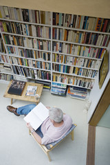 Man looking at a book in home library