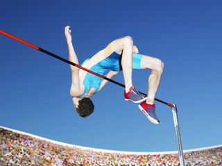 Athlete high jumping in an arena