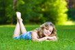 Young woman lying on a green grass