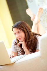 Junge Frau mit Laptop am Sofa liegend