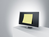 Monitor on a podium with oversized post it note.