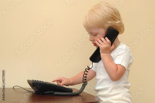 Child presses buttons of the telephone