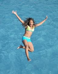 jugendliches Mädchen springt rücklings ins Pool