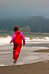 young girl in red raingear skips on ocean beach.  USA