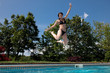 Woman in black bikini jumping into pool
