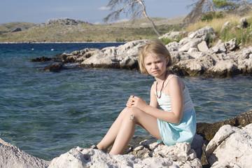 little girl sitting on a rocks
