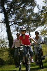 couple avec une jeune fille faisant du vélo à la campagne