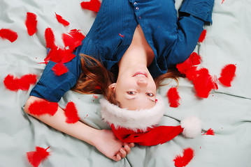 Adorable girl with santa hat laying on bed