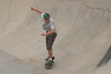 teenage skateboarder riding in cement half pipe