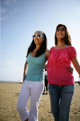 Femmes souriantes se promenant à la plage