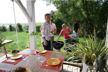 groupes d'amis cuisant des brochettes de viande au barbecue