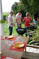 deux couples cuisant des brochettes de viande au barbecue