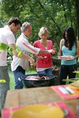 Hommes et femmes cuisant des brochettes