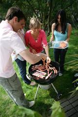 Hommes et femmes cuisant des brochettes de viande au barbecue