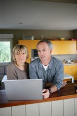 couple devant un ordinateur portable dans une cuisine