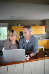 homme et femme devant un ordinateur portable dans une cuisine