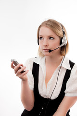 young woman with headset and mobile looks disinterested