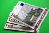 three 5 euro banknote on the green background