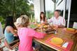 Hommes et femmes à table en terrasse dans un jardin