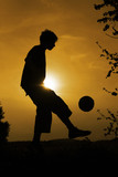 A boy is playing soccer in the sunset