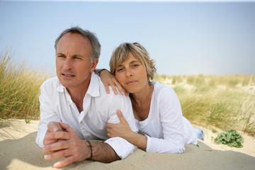 Portrait d'un homme et d'une femme étendus sur le sable