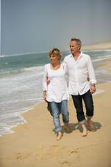 Homme et femme se promenant au bord de la plage