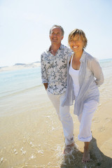 homme et femme souriants se promenant au bord de la plage