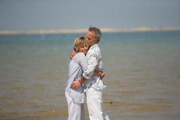 Homme et femme s'enlaçant au bord de la plage