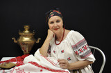 Lady embroiderer in traditional Ukrainian clothes on black